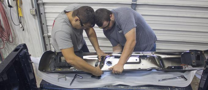 two male students working on a bumper