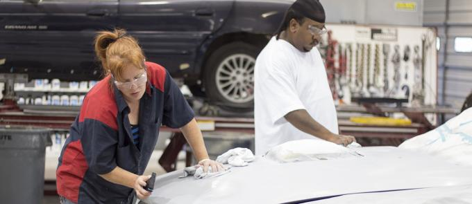 two students sanding a car before painting